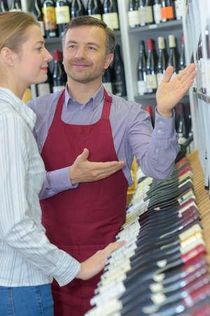 vendedor que recomienda vino a una clienta