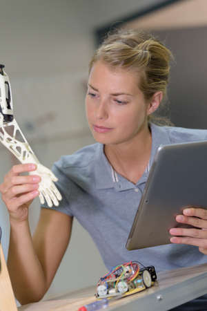 woman holding tablet looking at robotic hand Stock Photo
