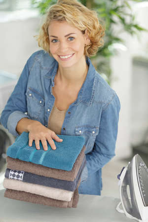 smiling woman holding pile of ironed towels 写真素材