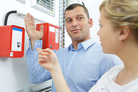 man explaining emergency alarm system to female colleague