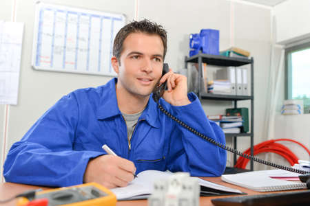 Man in overalls on telephone