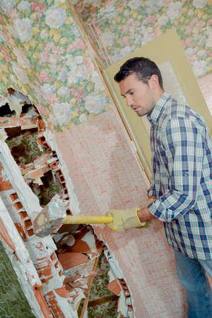 Worker demolishing a partition wall Stockfoto