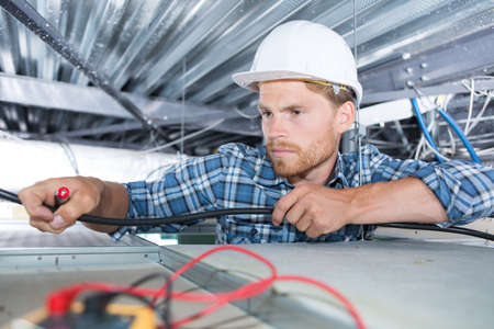 Electrician reaching into roof space Stock Photo