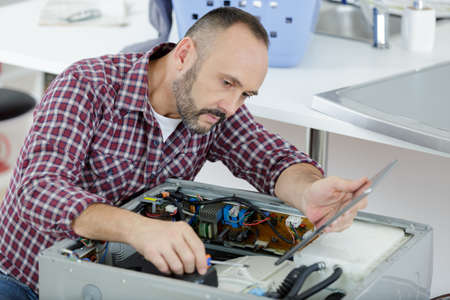 serviceman looking at tablet while repairing washing machine