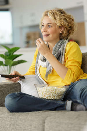 woman lying on sofa holding television remote control and popcorn
