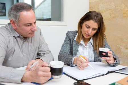 colleagues having a coffee while looking through notebook Banco de Imagens