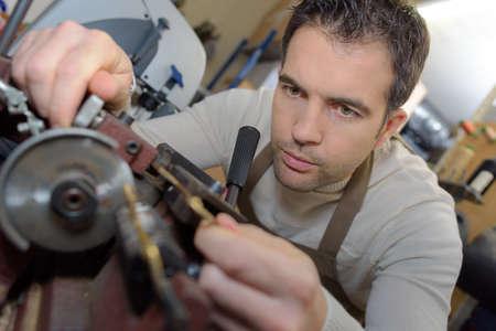 Man die op een bank gemonteerde grinder gebruikt Stockfoto