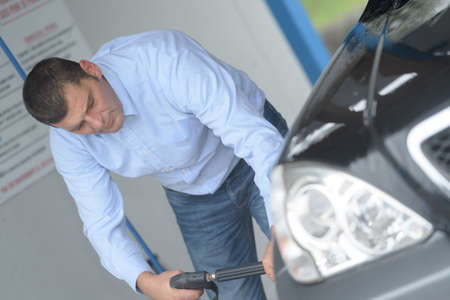 portrait of man cleaning his car Stock Photo