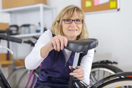 senior woman fixing a bike saddle Фото со стока