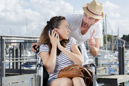 man gesturing to disabled girlfriend on telephone