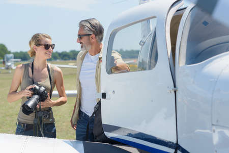 female photographer talking to man exiting private jet Stock fotó