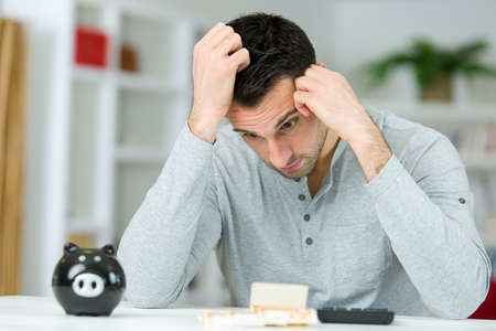 poverty stricken man with piggy bank and calculator