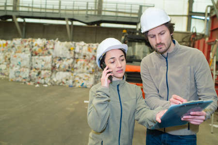 workers looking at clipboard and using telephone in recycling center