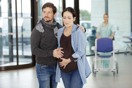 husband and pregnant woman in pain visiting doctor