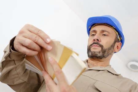 a painter holding color swatches Banco de Imagens