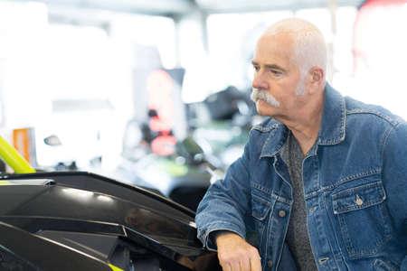 man testing motorcycle at showroom