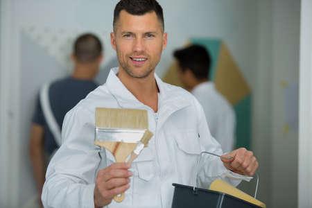 male painter holding different sized paintbrushes Banco de Imagens