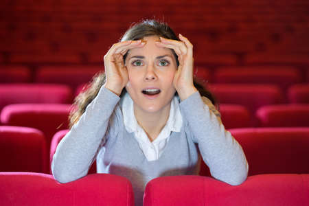 woman with shocking facial expression sitting at theater Stockfoto