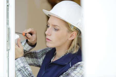 engineer builder woman working on a window