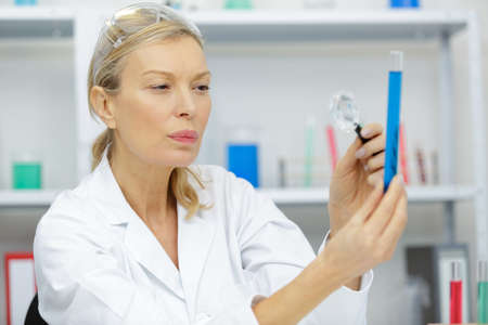 mature researcher using a magnifying glass on chemical liquids