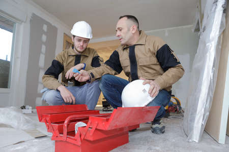 two builders crouched to open toolbox