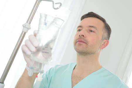 portrait of a male nurse adjusting a perfusion bag