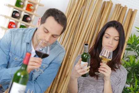 happy young couple tasting wine with merchant in foreground