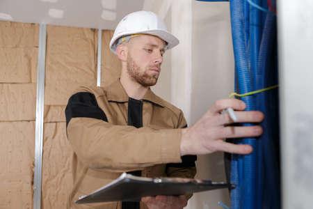 Techniker, der den Zustand der Wasserleitungen in Innenräumen überprüft