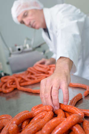 a butcher is making sausages