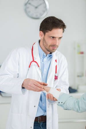 an adult doctor bandaging his patient in the hospital Banco de Imagens