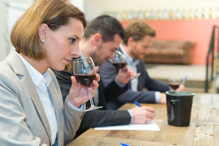 three young people taking notes while doing wine tasting