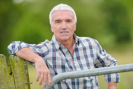 Portrait of man leaning on fencing post