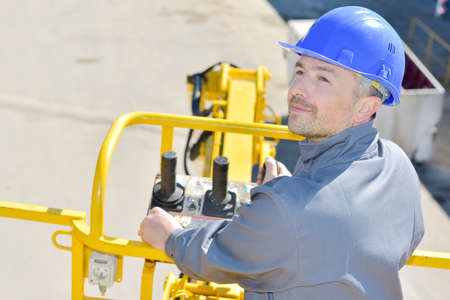 man controlling a yellow colored machine