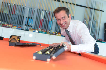 Portrait of man opening box containing pool cue