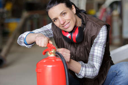 woman using a fire extinguisher