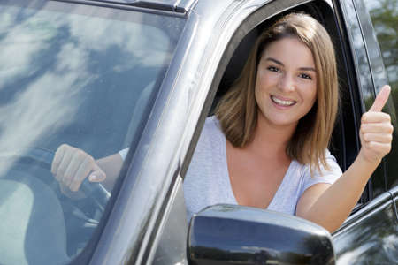 woman sitting in the car and showing thumbs up