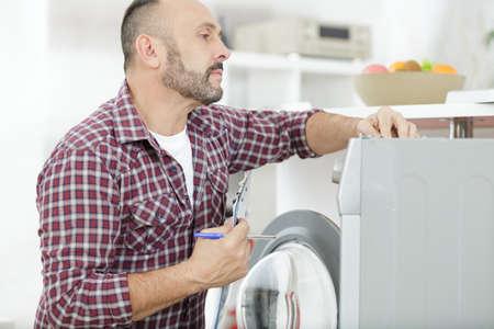 man with clipboard near washing machine Reklamní fotografie