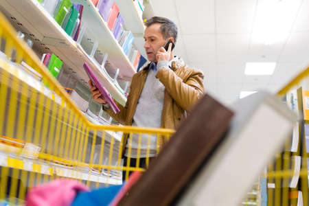 man on the phone buying folders in a store