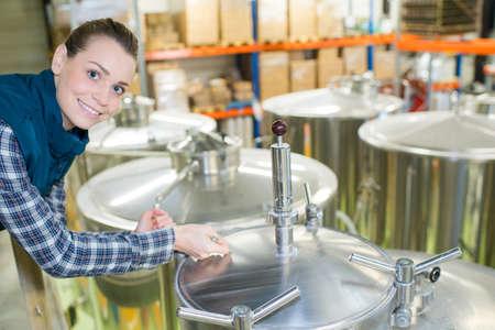 ritratto di donna in fabbrica di birra stava accanto a tini