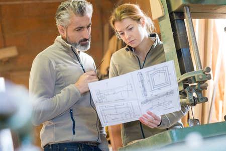 cabinet makers looking at project drawings Banco de Imagens