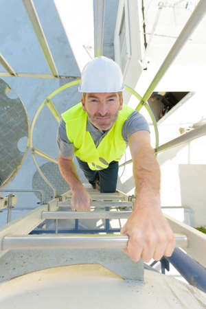 portrait of confident male worker walking up stairs in industry