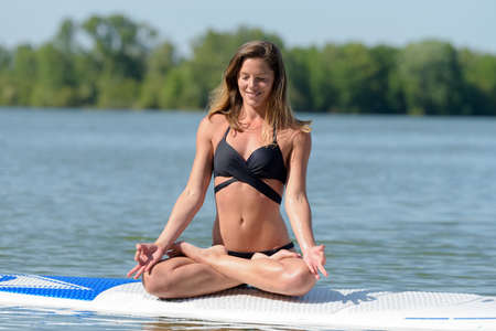 woman practicing yoga on a paddle board 免版税图像