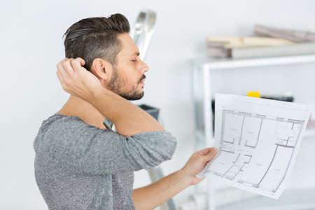 man in apartment looking at floorplan designs
