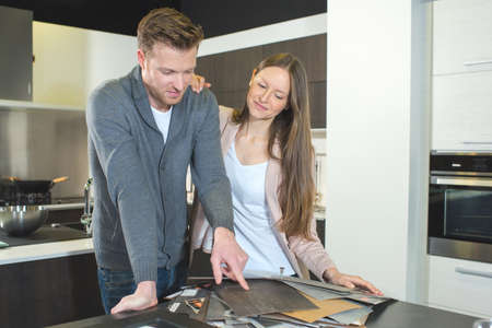 couple choosing kitchen design from samples