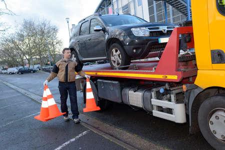 Mann, der ein Auto schleppt