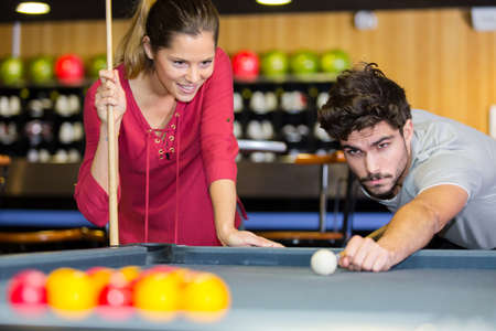young couple playing pool in the bar