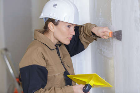 female plasterer painter at indoor wall