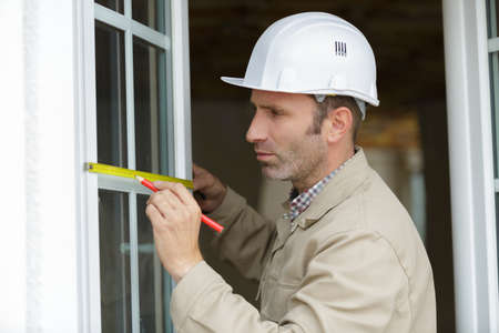 male builder is measuring a window