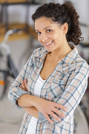 young woman standing with crossed arms and smiling at camera