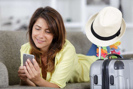 woman texting on sofa before travelling